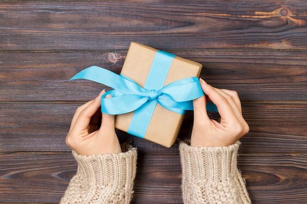 Mãos de mulher dão namorados embrulhados ou outro presente artesanal de férias em papel com fita azul