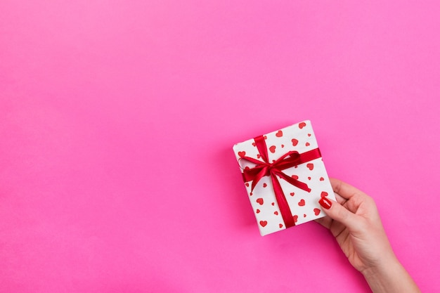 Mãos de mulher dão vista superior da caixa de presente presente