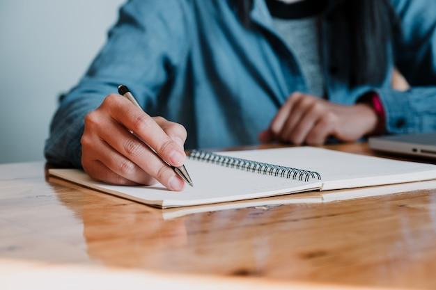 Mãos de mulher de negócios com caneta escrevendo notebook