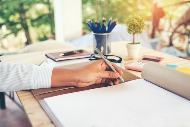 Mãos de mulher de negócios escrevendo no caderno.