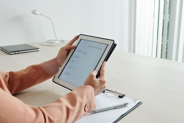 Mãos de mulher de negócios inserindo informações pessoais no formulário de curriculum vitae no tablet digital