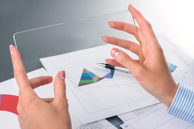 Mãos de mulher de negócios segurando um tablet de vidro. mãos femininas com tablet transparente. é capaz de muitas coisas. protótipo do futuro.