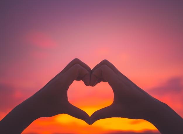 Mãos de mulher de silhueta para ser a forma de coração no fundo por do sol.