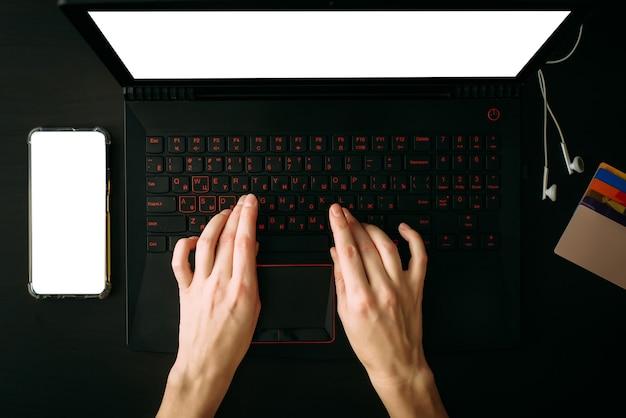 Mãos de mulher de vista superior digitando no laptop com tela branca em branco. smartphone com tela vazia, fones de ouvido, cartões de crédito na mesa preta