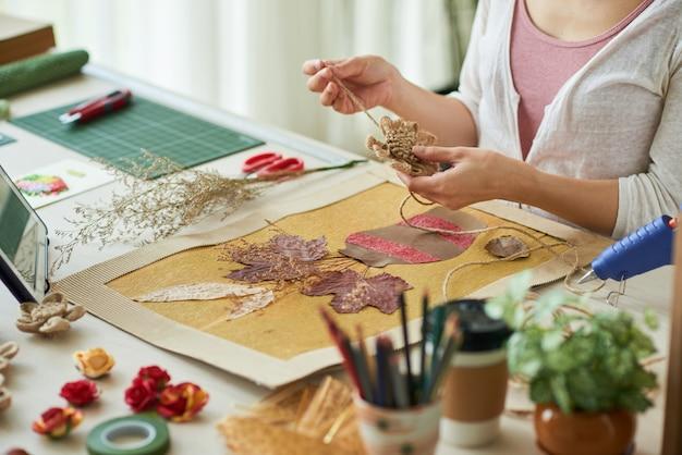 Mãos de mulher decorando obras de arte em estilo oshibana com flores feitas de corda de linho