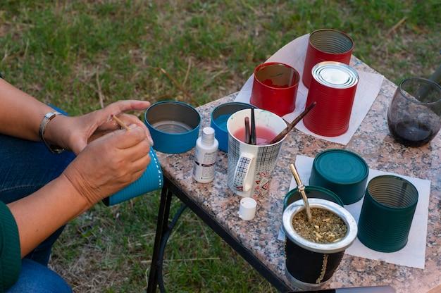 Mãos de mulher decorando recipientes de metal com tintas coloridas. mãos de mulher decorando recipientes de metal com tinta colorida