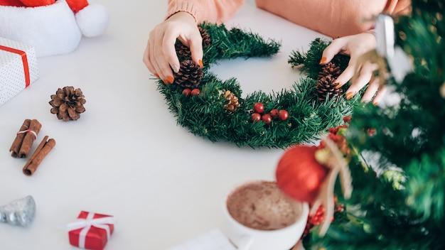 Mãos de mulher, decorar a árvore de natal e guirlanda de natal.