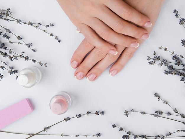 Mãos de mulher deitada plana com ferramentas de manicure