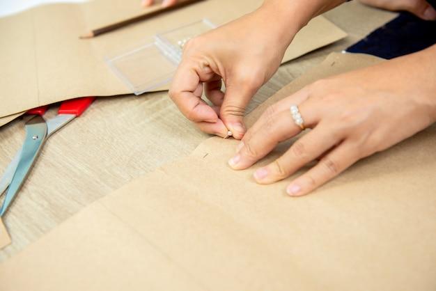 Mãos, de, mulher, desenhista, fixando, padrão papel, ligado, tecido