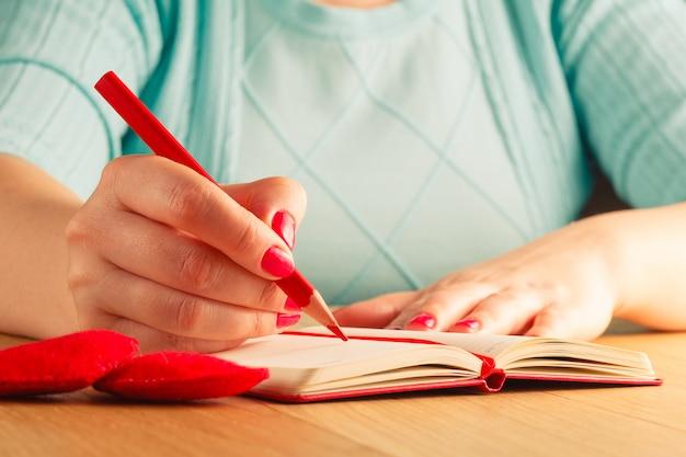 Mãos de mulher, desenho ou escrita, caixa de presente, corações vermelhos na mesa de madeira