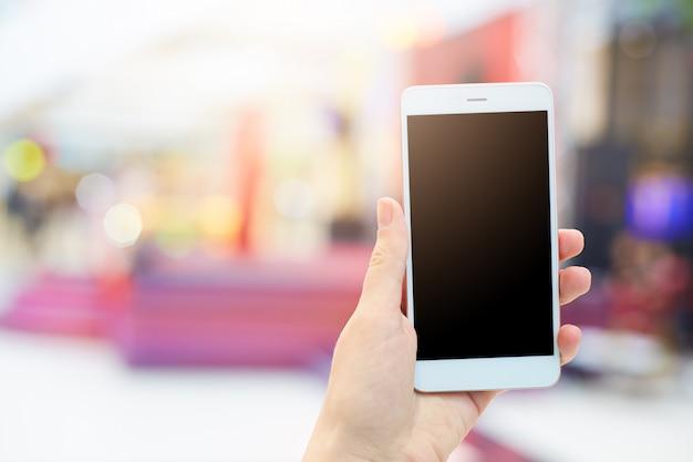 Mãos de mulher detém moderno aparelho eletrônico. fêmea irreconhecível com celular branco