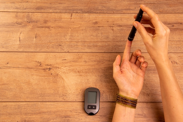 Mãos de mulher diabética, usando dispositivos para medir a glicose no sangue.