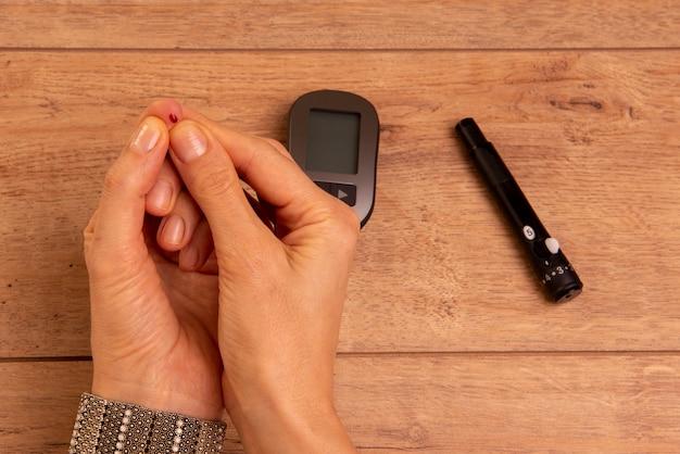 Mãos de mulher diabética usando o glicosímetro para medir a glicose no sangue.