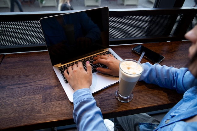 Mãos de mulher digitando no laptop
