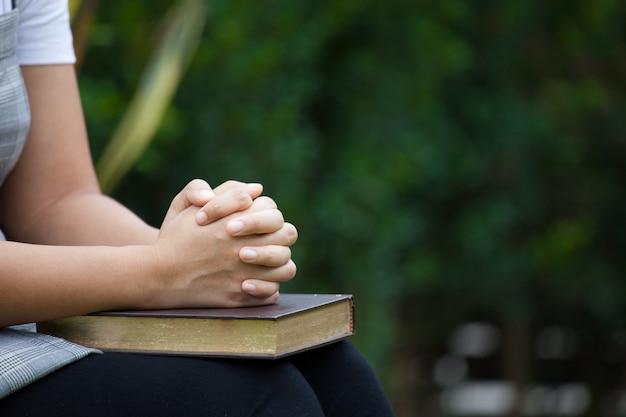 Mãos de mulher dobradas em oração em uma bíblia sagrada para o conceito de fé na natureza fundo verde