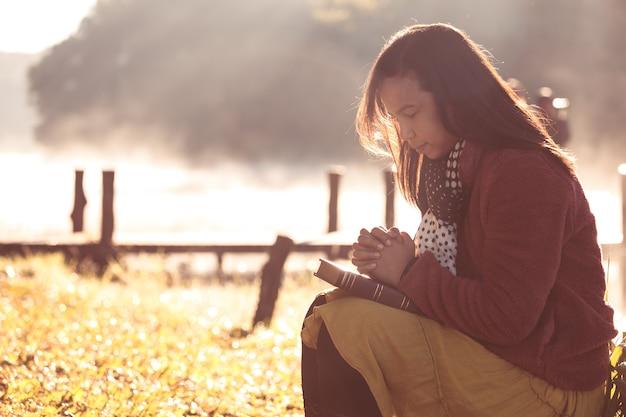 Mãos de mulher dobradas em oração sobre uma bíblia sagrada para fé em fundo de natureza bela