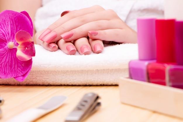 Mãos de mulher durante a sessão de manicure