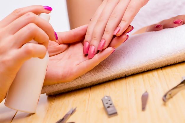 Mãos de mulher durante o procedimento de manicure