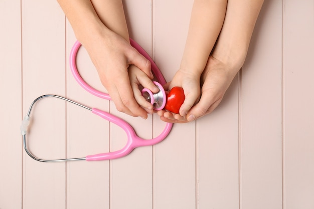 Mãos de mulher e criança com coração vermelho e estetoscópio na madeira.