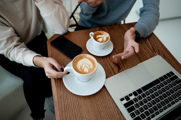Mãos de mulher e de homem holhs xícaras de cappuccino ou branco liso. vista de corte superior. laptop moderno na mesa de madeira. duas pessoas discutindo algo com expressão. conceito de cafeteria.