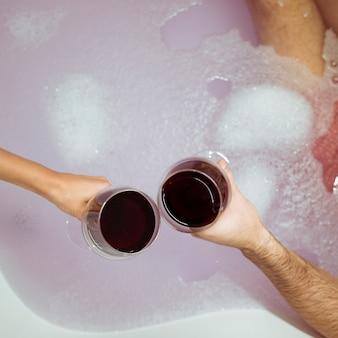 Mãos de mulher e homem com copos de bebida perto da água com espuma