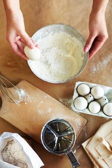Mãos de mulher e ingredientes de panificação