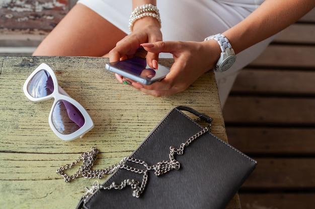 Mãos de mulher elegante usando smartphone