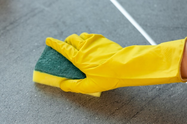 Mãos de mulher em luvas amarelas limpando a bancada da cozinha close-up