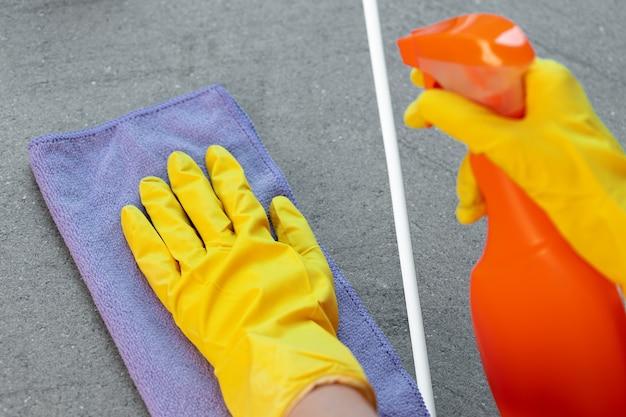 Mãos de mulher em luvas amarelas limpando a bancada da cozinha