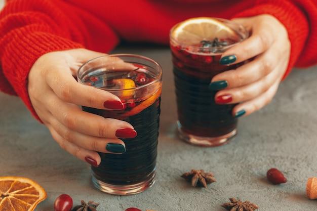 Mãos de mulher em suéter quente segurando uma xícara de vinho quente