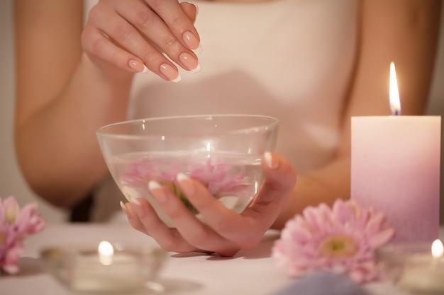 Mãos de mulher em um salão de beleza recebendo uma esfoliação da mão descascando por uma esteticista. manicure spa, massagem das mãos e cuidados com o corpo, tratamentos de spa.