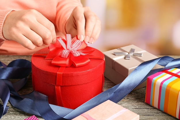 Mãos de mulher empacotando presentes para o feriado
