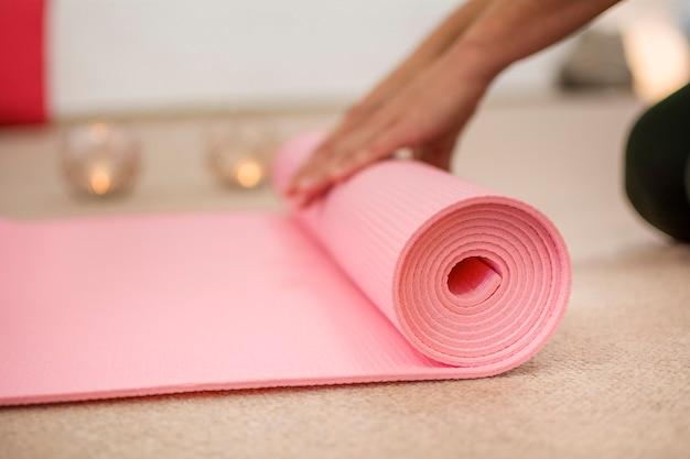 Mãos de mulher enrolando o tapete de ioga rosa.