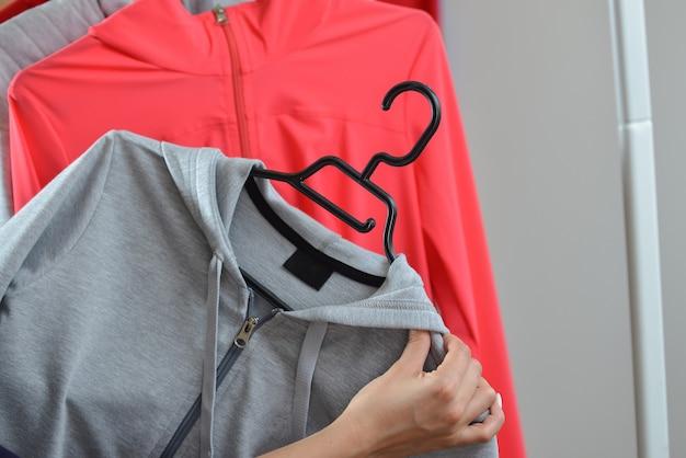 Mãos de mulher escolhendo uma jaqueta esportiva na loja