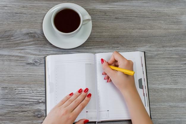 Mãos de mulher escrevendo informações em um bloco de notas. a xícara de chá está no fundo. visão aérea, copie o espaço