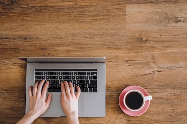 Mãos de mulher estão digitando em um notebook em uma mesa de madeira com uma xícara de café.