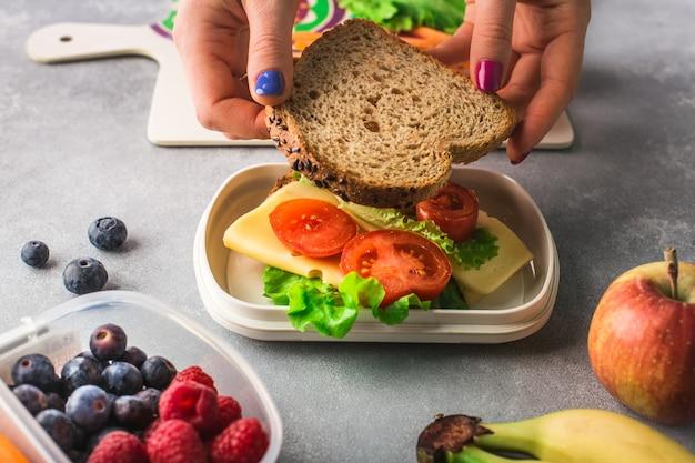 Mãos de mulher estão fazendo sanduíche de vegetais e queijo para a lancheira
