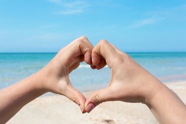 Mãos de mulher fazendo formato de coração na praia