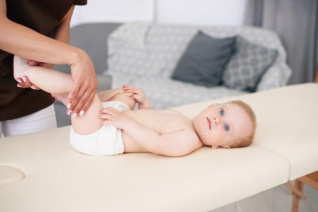 Mãos de mulher fazendo massagem para um bebê. cuidados de saúde e conceito médico.