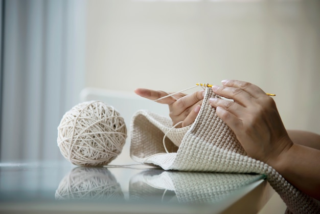 Mãos de mulher fazendo trabalho de tricô em casa