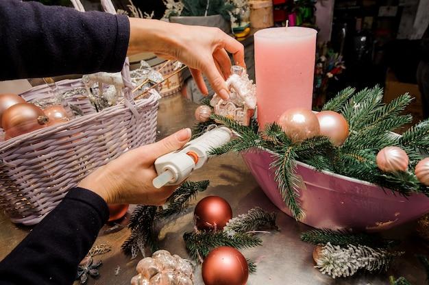 Mãos de mulher fazendo uma bela composição de decoração de natal