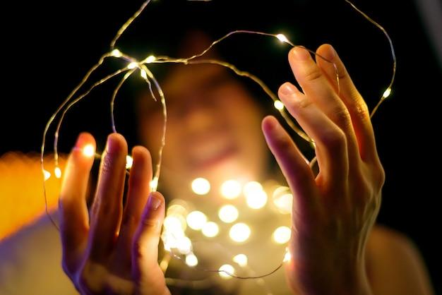 Mãos de mulher feliz segurando a luz amarela de natal, fundo de bokeh