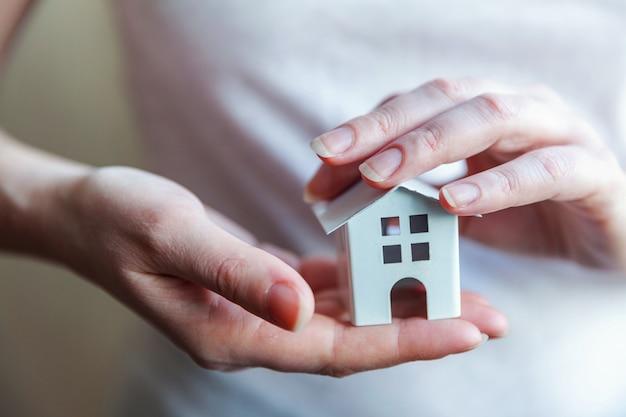 Mãos de mulher feminina segurando a casa de brinquedo em miniatura branco
