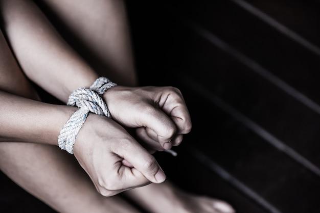 Mãos de mulher foram amarradas com uma corda. violência, apavorada, conceito do dia dos direitos humanos.