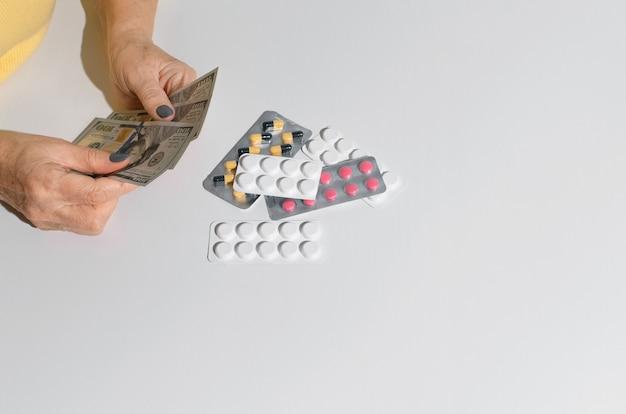 Mãos de mulher idosa segurando dinheiro. comprimidos na vista superior de mesa branca, copie o espaço. conceito de custo do tratamento, preço do medicamento, orçamento do seguro saúde