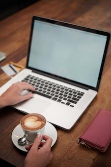 Mãos de mulher irreconhecível com cappuccino e laptop sentado à mesa de madeira