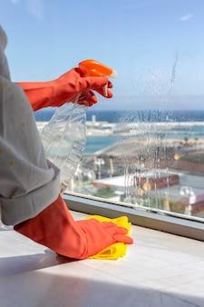 Mãos de mulher irreconhecível com luvas de proteção para limpar a casa