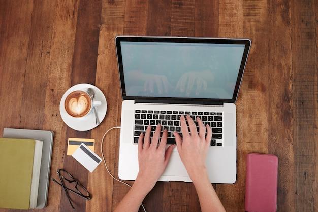 Mãos de mulher irreconhecível, trabalhando no laptop, com cappuccino e cartões de crédito na mesa
