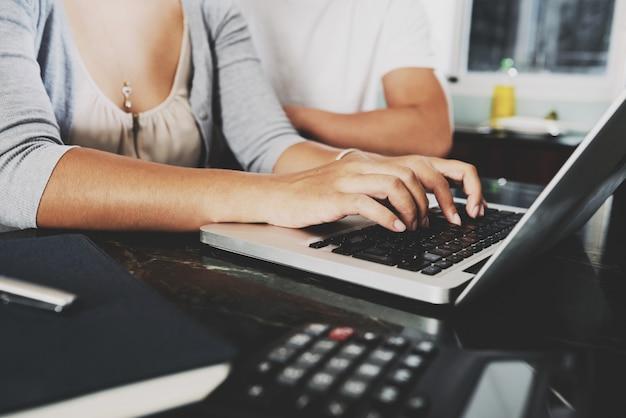 Mãos de mulher irreconhecível, trabalhando no laptop em casa e homem sentado ao lado