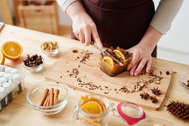 Mãos de mulher jovem com faca cortando sabonete artesanal grande com especiarias aromáticas e fatias de laranja na placa de madeira